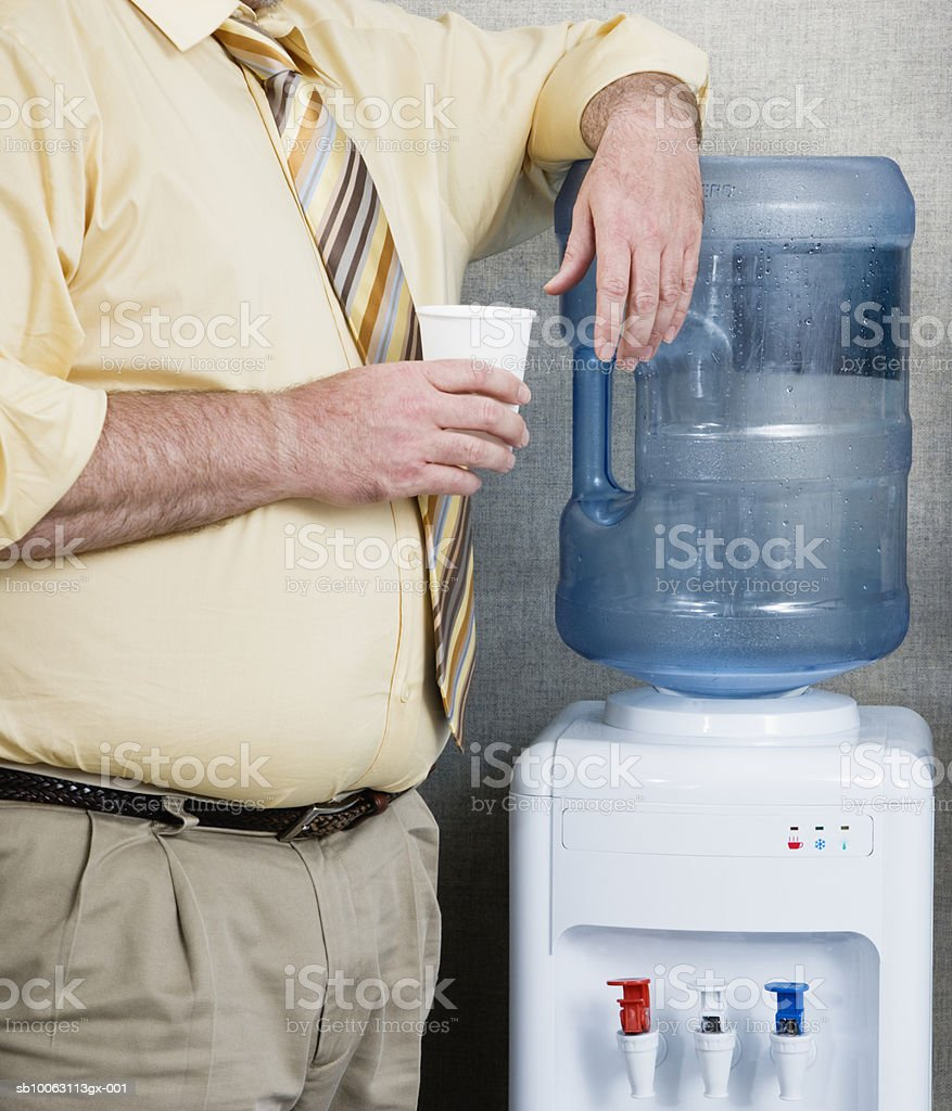 Man drinking water from water cooler, mid section foto de stock libre de derechos