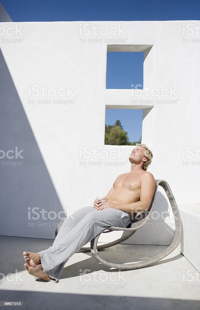 Man drinking water in chair on patio royalty-free stock photo