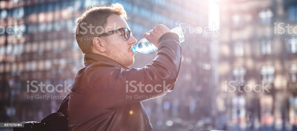 Man drinking water in the city stock photo