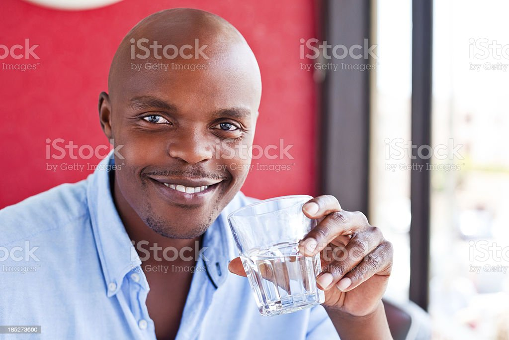 Man drinking water A handsome african man holding glass of water in his hand, smiling at camera. Adult Stock Photo