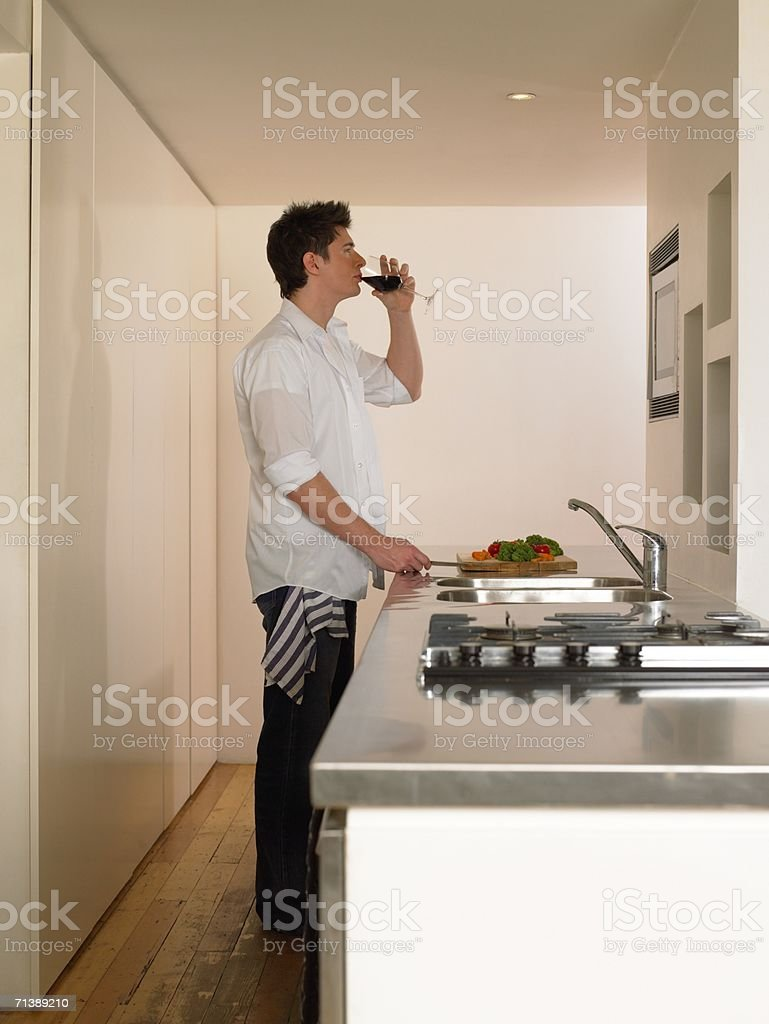 Man drinking wine in kitchen royalty-free stock photo