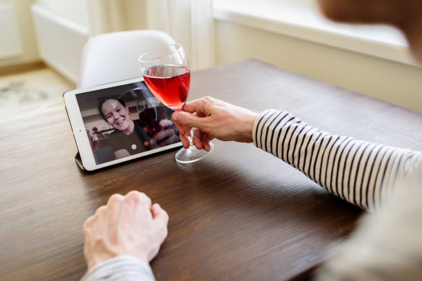 Man drinking wine online with female friend