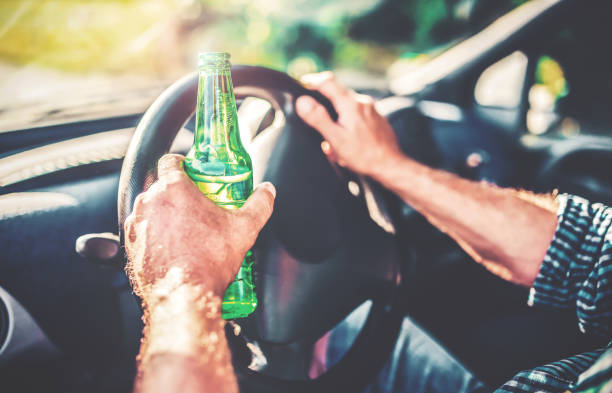 A man drinks beer while driving a car. Dangerous driving stock photo