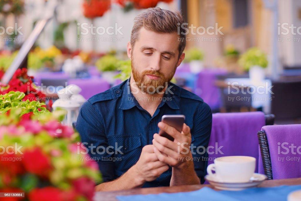 En man dricker kaffe och med en smartphone i ett café. - Royaltyfri Blomma Bildbanksbilder