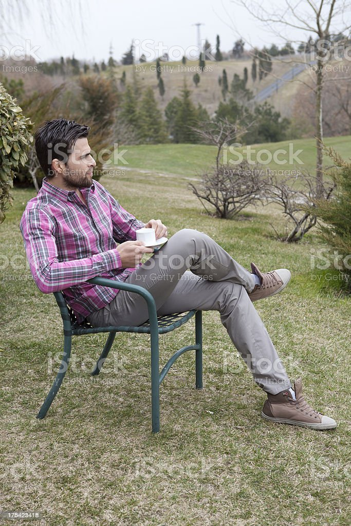 Man drinks coffee in a park royalty-free stock photo