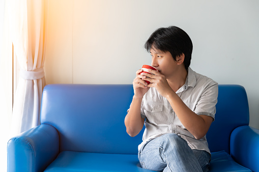 530281733 istock photo A man drinks coffee in the morning while sitting on the blue sofa. He looks at outside and thinks to find creative ideas and inspiration 1130950062