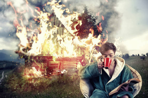 Man drinks coffee Man drinks coffee and reading a book while his house is on fire, on a mountain background. Concept of a careless man. careless stock pictures, royalty-free photos & images