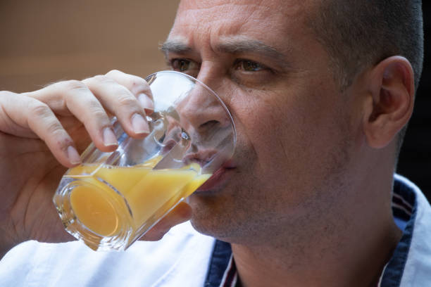 A man drinks his juice, head only. stock photo