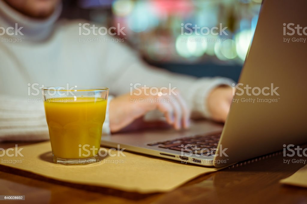 man drinks juse while working on laptop stock photo