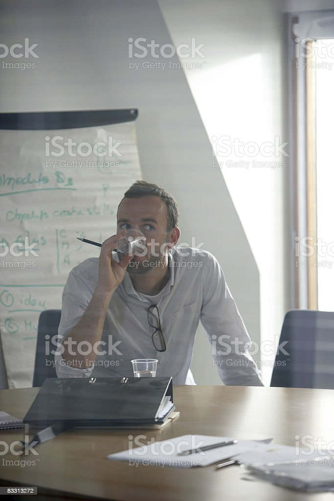 man drinks water during office meeting royaltyfri bildbanksbilder