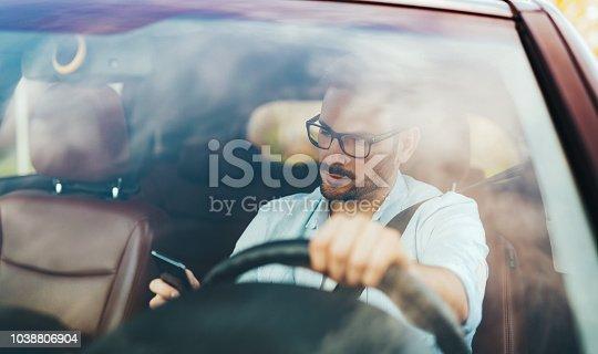 istock Man driver using smart phone in car modern 1038806904