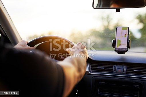 A man drives his car at sunset