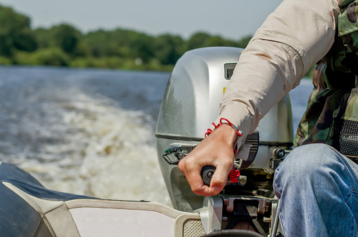 A man drives a motor boat. Speed boat.