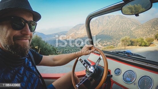 Man drives a car, view of the road, mountains in background