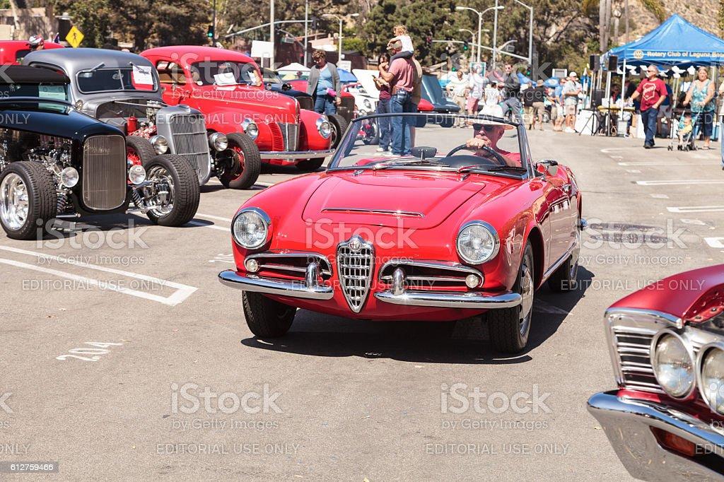 Man drives a red classic Alfa Romeo Milano car stock photo