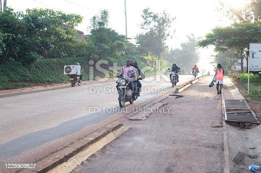 Kampala, Uganda - January 13th, 2020: Unidentified man drives his bike with two passengers down a street in Kampala, Uganda. Motorcycle taxi (