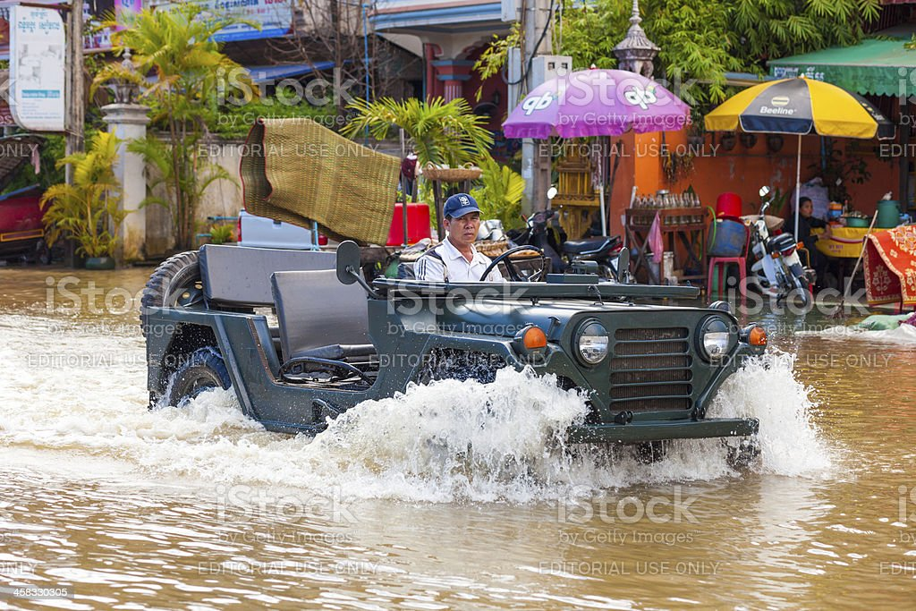 Man drives through floodwaters, Siem Reap, Cambodia royalty-free stock photo