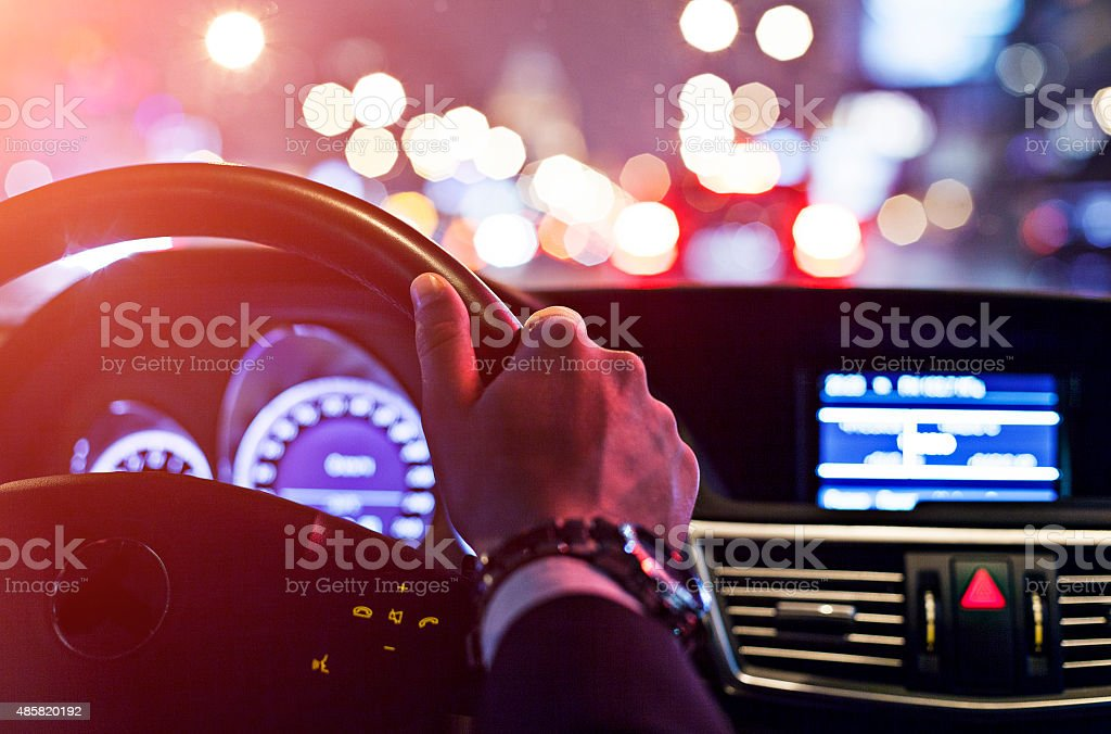 man driving a car at night stock photo
