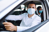 istock Man driving a car in protective sterile medical mask during an epidemic in quarantine city. Covid- 19. 1279184837