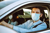 istock Man driving a car puts on a medical mask during an epidemic in quarantine city. 1248778884