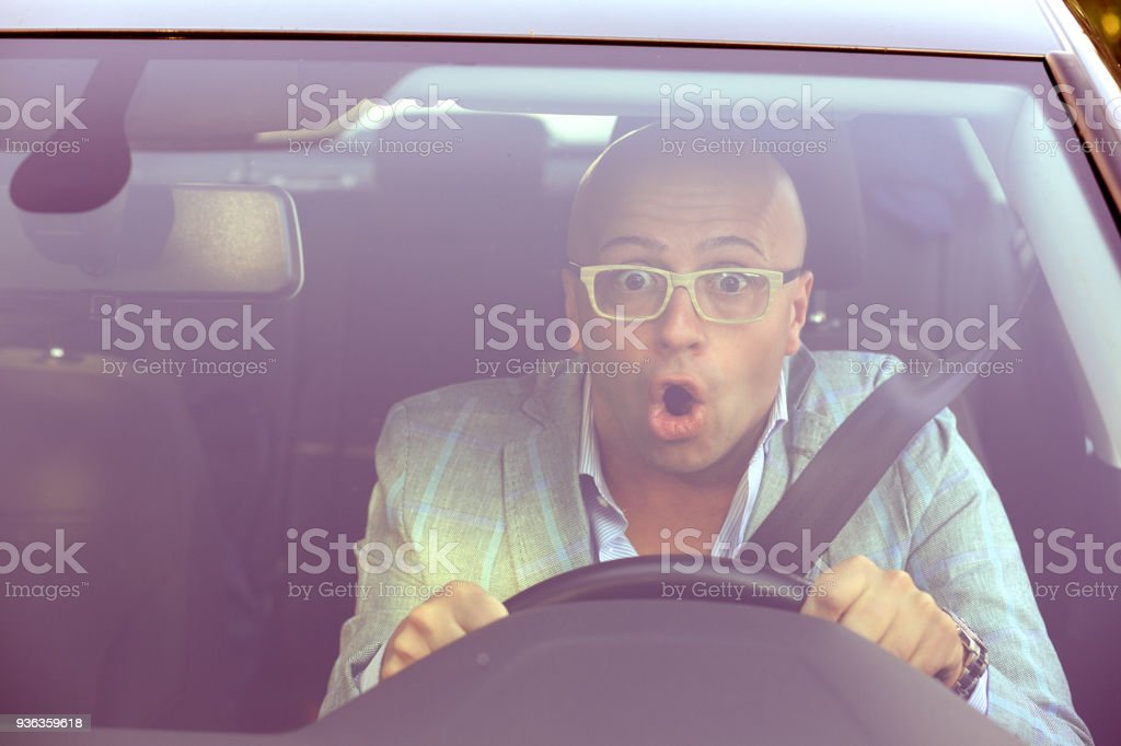 Man driving a car shocked about to have traffic accident, windsh stock photo