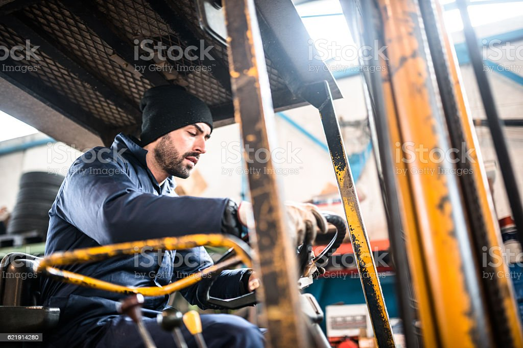 man driving a forklift stock photo