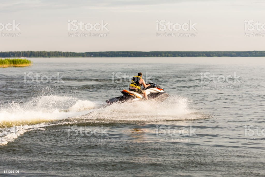 A man driving a jet ski , stunting and making spray of water drops stock photo