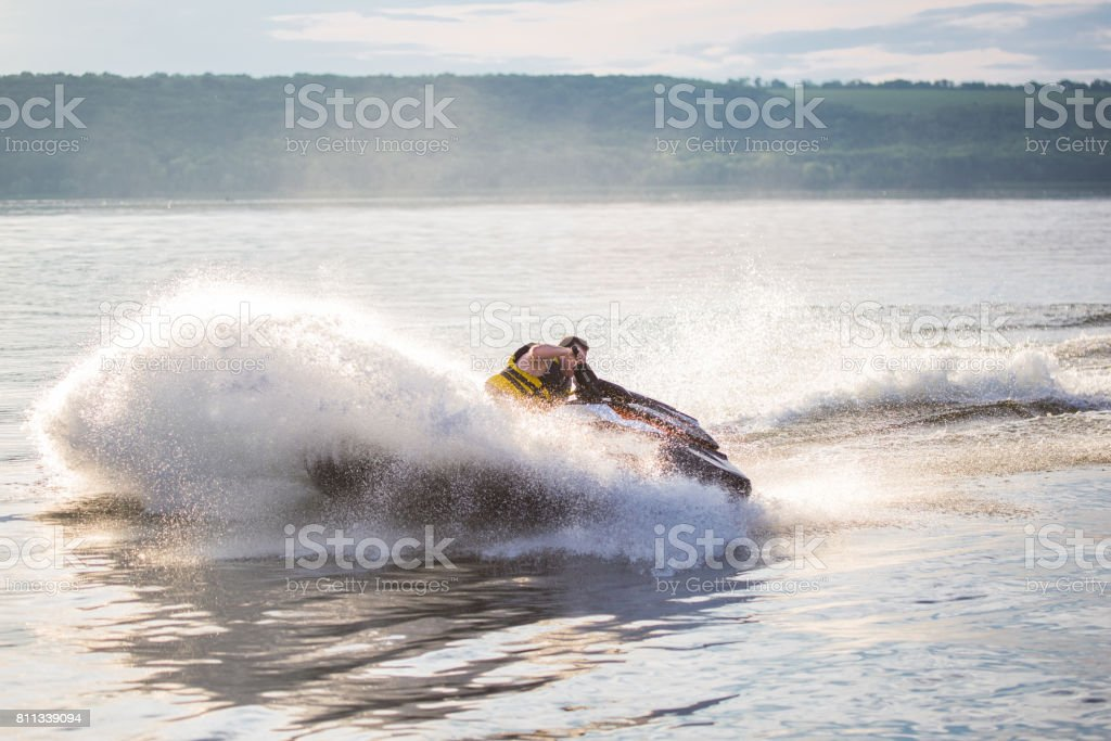 A man driving a jet ski , stunting and making spray of water drops with a sunlight on background stock photo