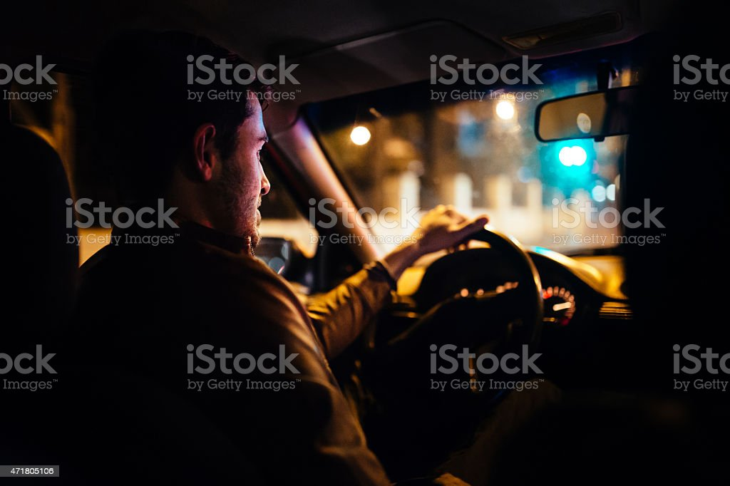 Man driving a private taxi through city streets at night stock photo