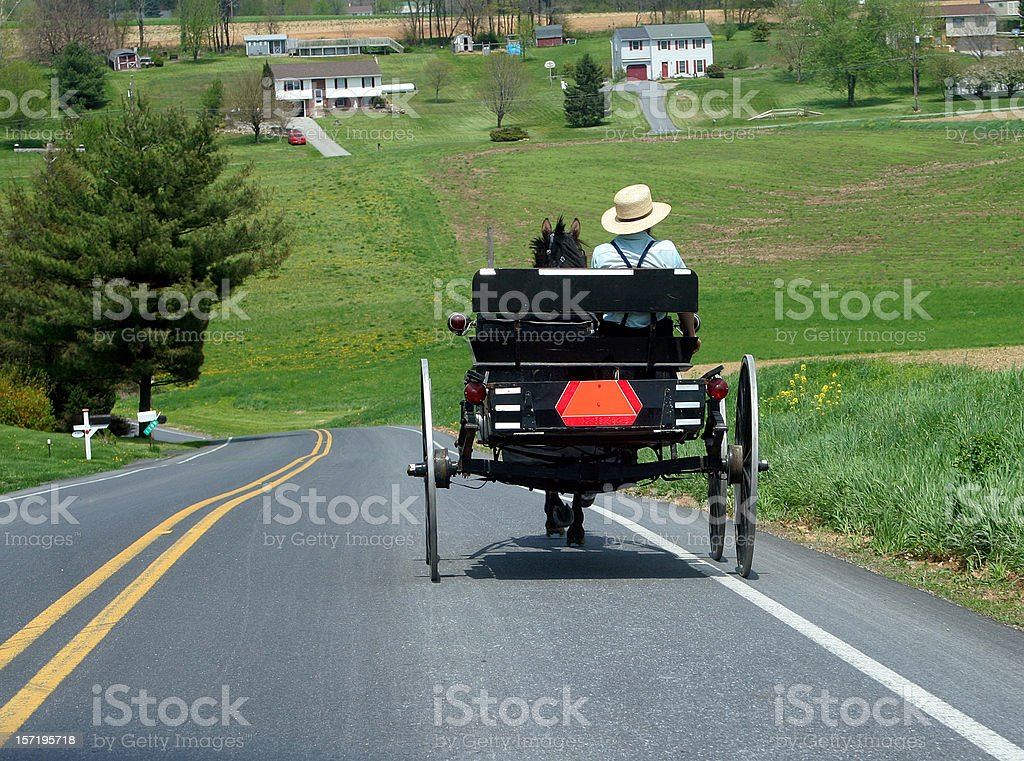 A man driving an Amish buggy down a sloping road stock photo