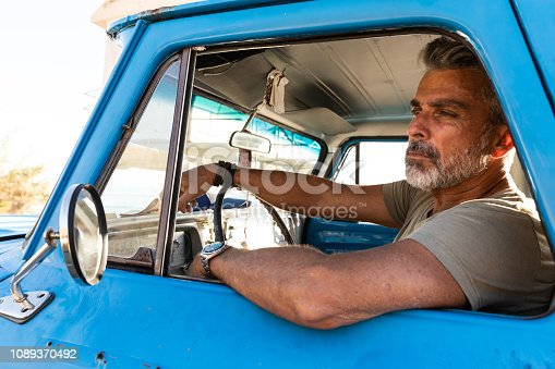 Man driving an old pick-up truck in California roads