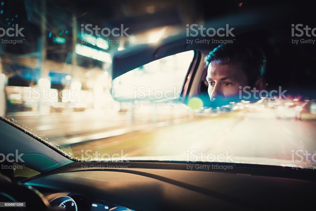 Man driving at night in the city stock photo