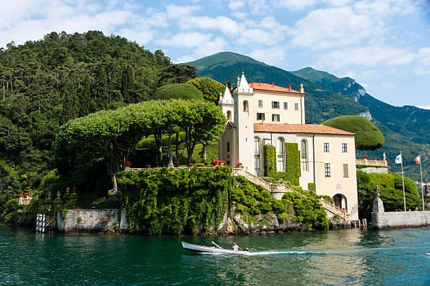 man driving boat in front of lake side villa -xxxl - como italië stockfoto's en -beelden