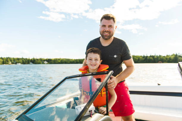 man driving boat on holiday with his son kid - sail stock pictures, royalty-free photos & images