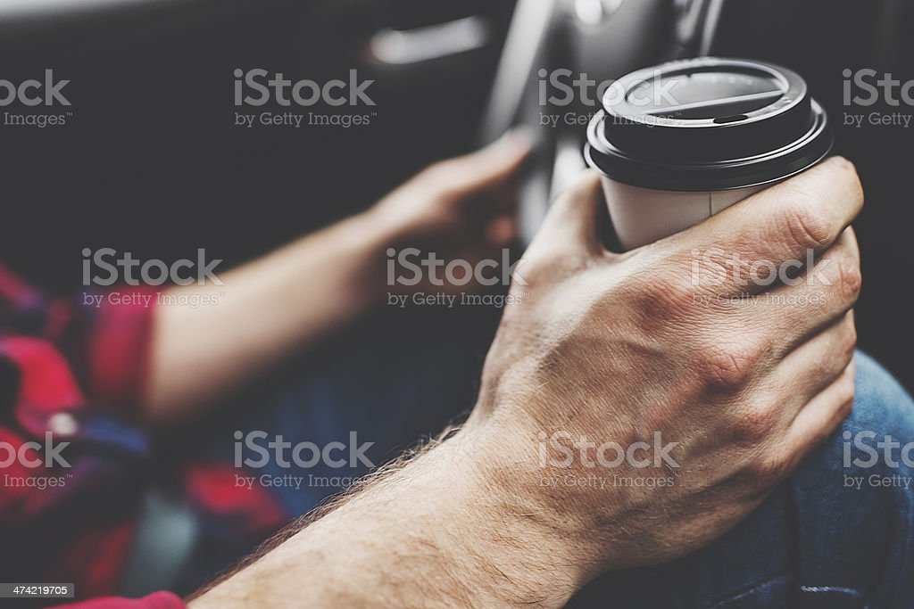 Man driving car and drinking coffee stock photo