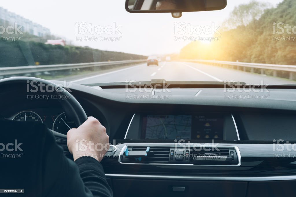 man driving car from rear view stock photo