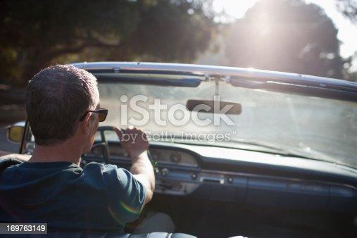 istock Man driving convertible car 169763149