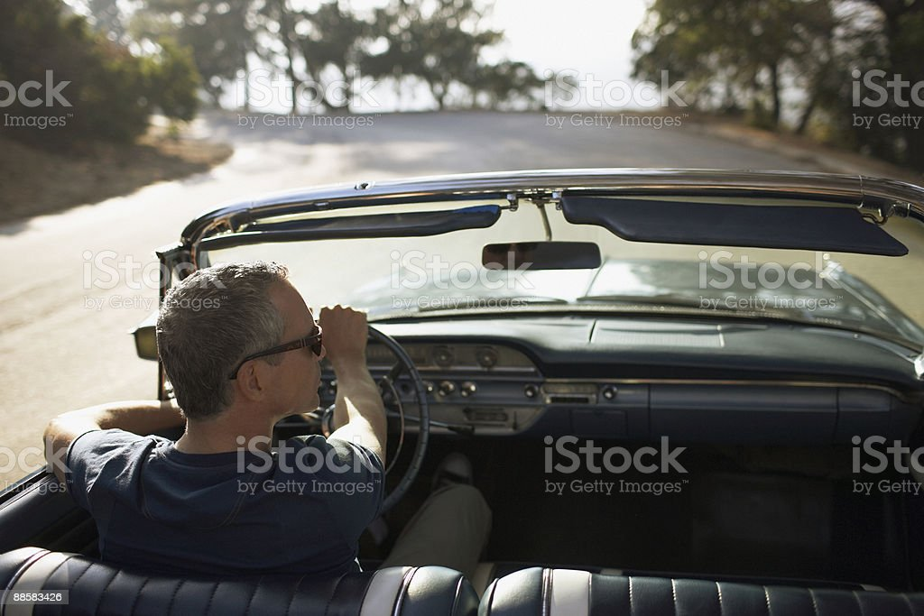 Man driving convertible car stock photo