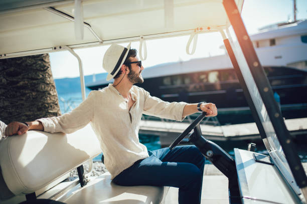 Man driving electric golf car on the dock by the sea Man driving electric golf car on the dock by the sea golf cart stock pictures, royalty-free photos & images