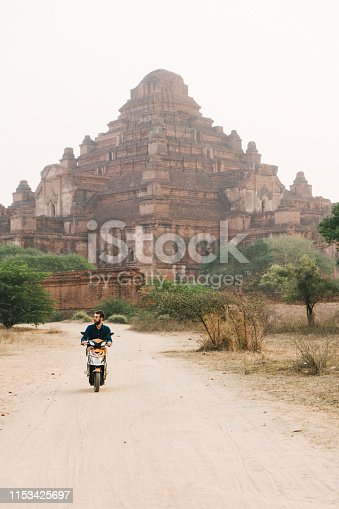 Young Caucasian man driving electro scooter in Bagan Heritage Site