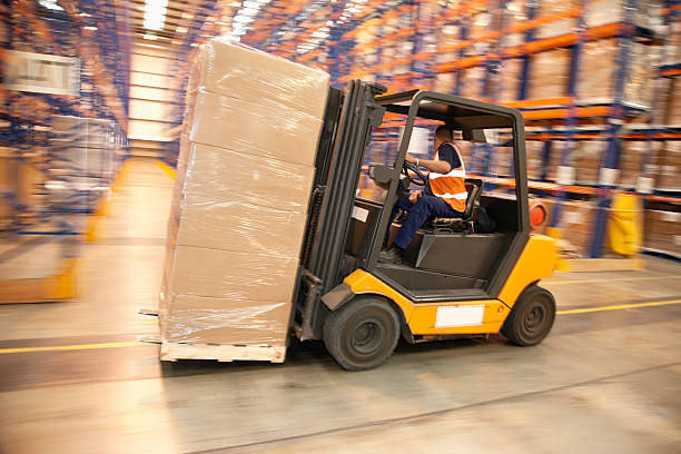 Man driving forklift in warehouse stock photo