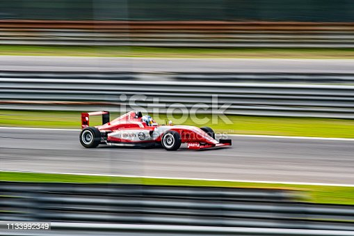 Blurred motion of man driving formula racing car on motor racing track.