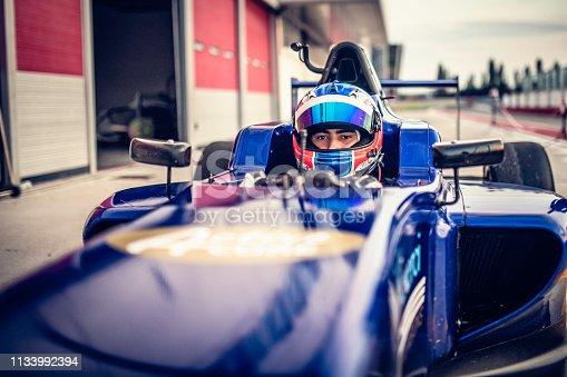 Man driving formula racing car on motor racing track.