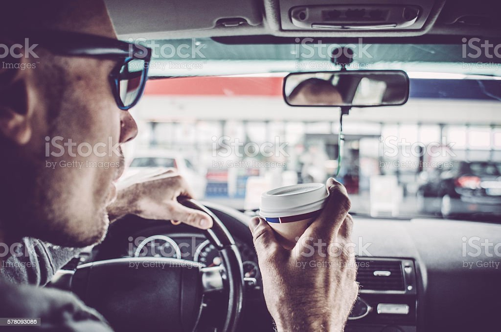 Man driving his Car and drinking take away coffee stock photo