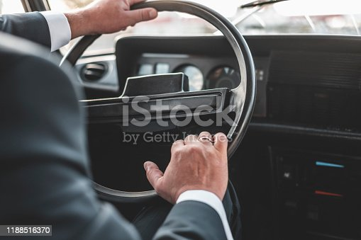 Man's hands holding steering wheels in a retro car.