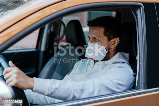 istock Man driving his car with a protection mask in the city 1212408696