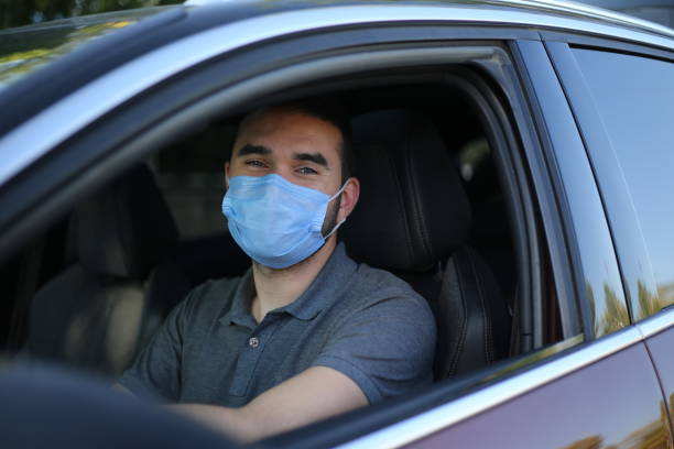 Man driving his car with a protection mask in the city stock photo