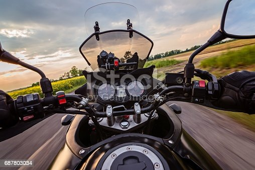 istock Man driving his motorcycle on asphalt country road 687803034