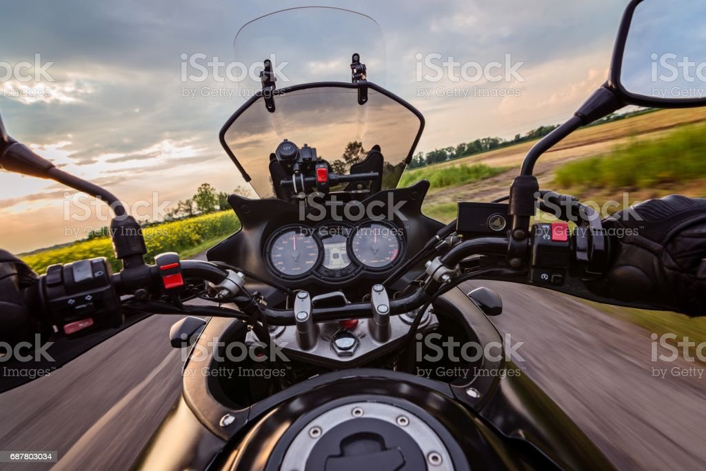 Man driving his motorcycle on asphalt country road stock photo