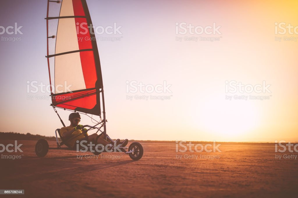 Man driving land sailing blokart on the beach at sunset stock photo